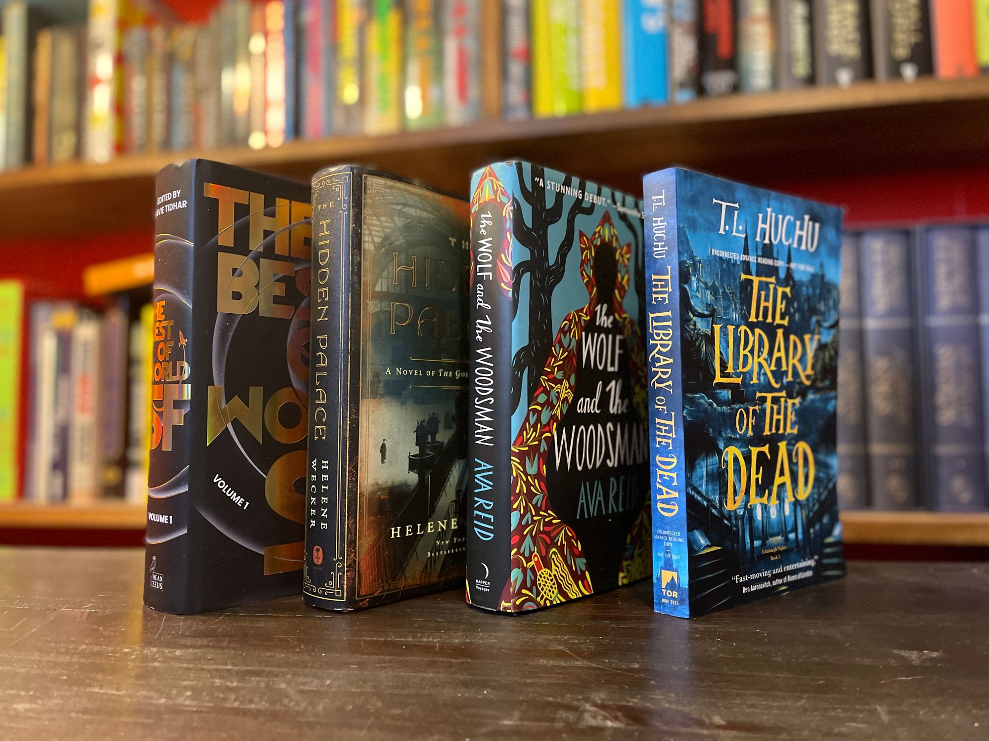 Four books standing up at an angle with a bookshelf in the background.